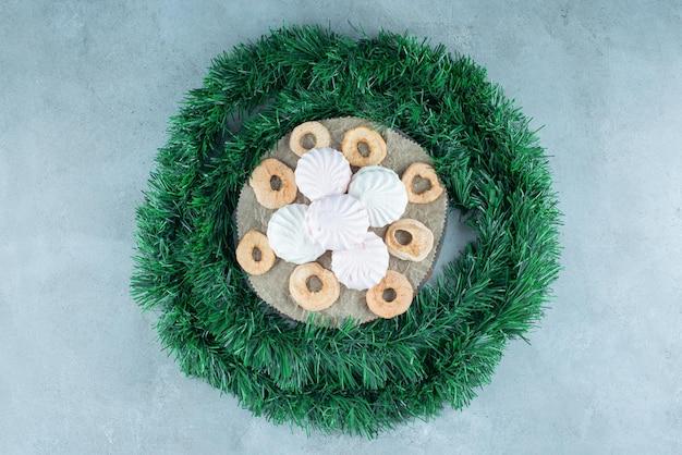Ghirlanda avvolta intorno a un tagliere con biscotti e fette di mela secche su marmo.