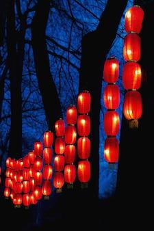 Гирлянды из красных китайских фонариков в парке вечером на фестиваль в китайский новый год