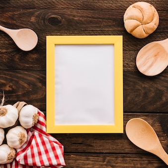 Garlic and bun near spoons and frame