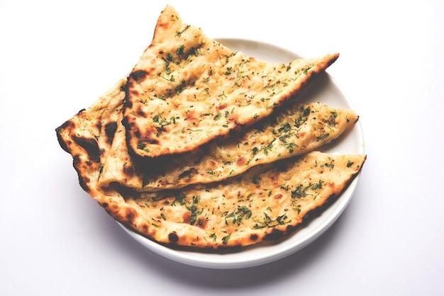 Наан с чесноком и кориандром подается в тарелке, это разновидность индийского хлеба или роти, приправленного лахсун.