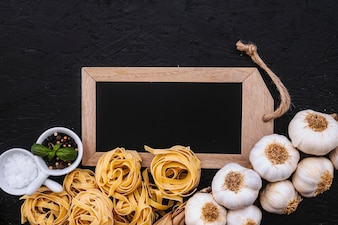 Garlic and pasta near spices and blackboard