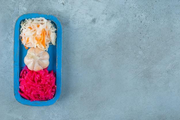 대리석 표면에 나무 접시에 마늘과 소금에 절인 양배추
