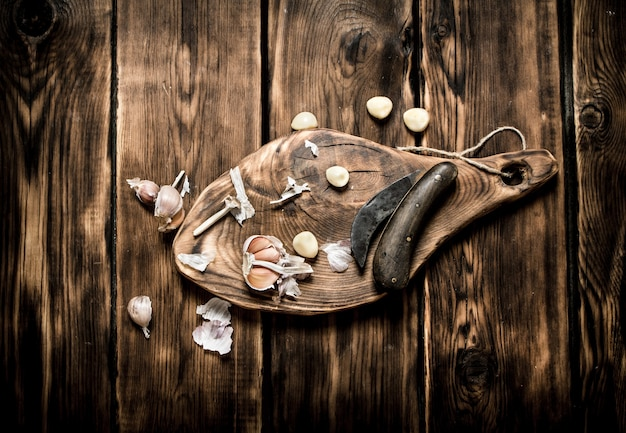 Фон чеснока. свежий чеснок на старой деревянной доске.