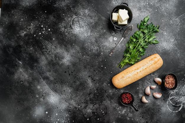 검은색 짙은 석재 테이블 배경에 있는 마늘 빵 복합 버터와 허브 재료 세트, 텍스트 복사 공간이 있는 평면도