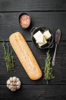 검은색 나무 테이블 배경에 있는 마늘 빵 복합 버터와 허브 재료 세트, 평면도