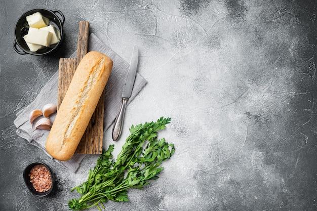 회색 석재 테이블 배경에 마늘 빵 복합 버터와 허브 재료 세트, 텍스트 복사 공간이 있는 평면도