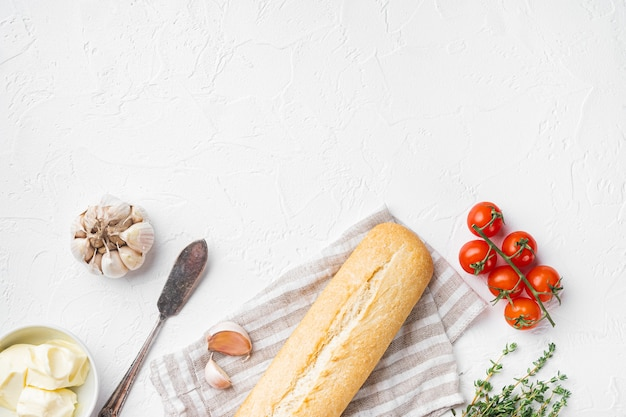 흰 돌 테이블 배경에 있는 마늘 빵 복합 버터와 허브 재료 세트, 텍스트 복사 공간이 있는 평면도