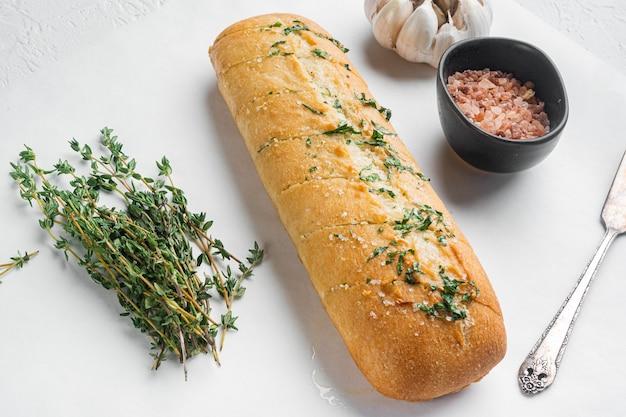 흰 돌 테이블 배경에 마늘 빵 가득 복합 허브 버터 세트