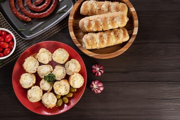 ソーセージ、チーズ、ローズマリー、オリーブ、チェリートマトを添えたバーベキューテーブルの赤いプレートにガーリックブレッド。上面図。