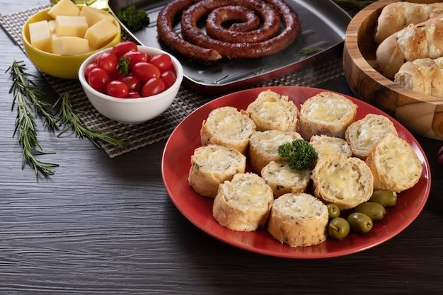 ソーセージ、チーズ、ローズマリー、オリーブ、チェリートマトを添えたバーベキューテーブルの赤いプレートにガーリックブレッド。