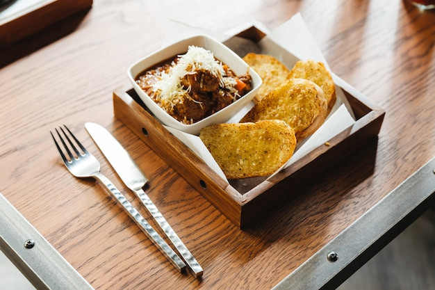 Garlic bread with meat sauce topping with mozzarella cheese, served on wooden box with knife and fork.