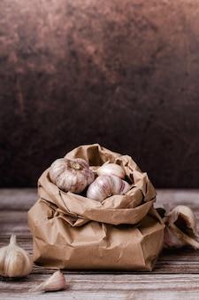 Луковицы чеснока в бумажном пакете на деревянном столе, вертикальный формат