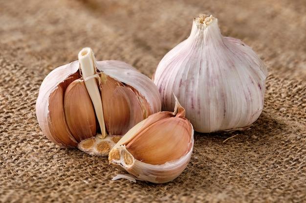 Garlic bulbs with cloves on sackcloth surface