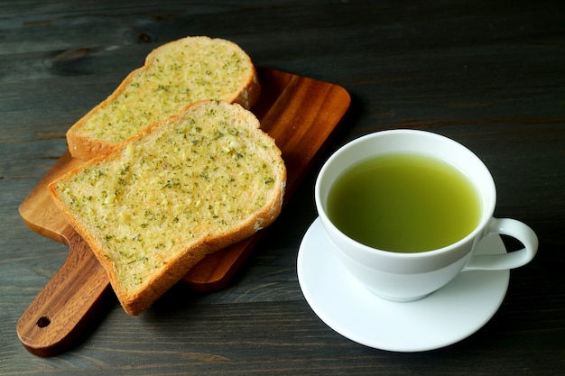 Garlic butter toasts on breadboard with a cup of hot green tea on black wooden table