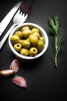 Garlic clove; bowl of olives and rosemary with cutlery on kitchen worktop