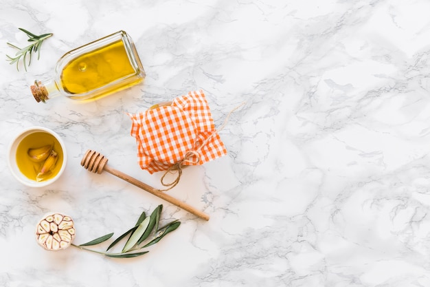 Garlic clove oil with jar on white marble backdrop
