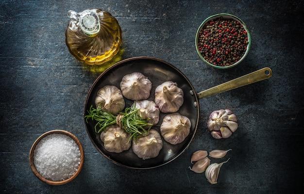 Зубчики и луковица чеснока в кастрюле со свежей солью оливкового масла розмарина и специями на бетонном столе - вид сверху.