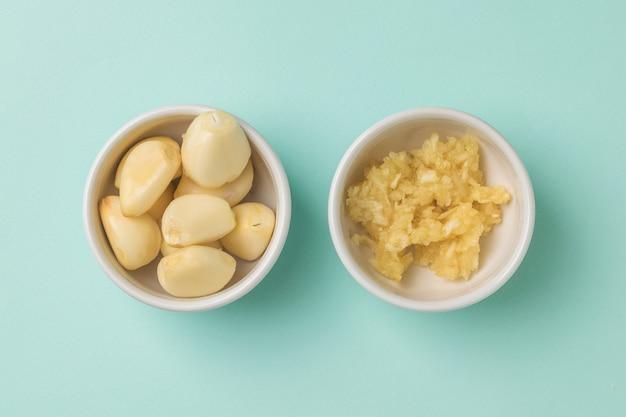 青い表面の白いボウルにニンニクのクローブとマッシュポテトのニンニク。キッチンに人気のスパイス。