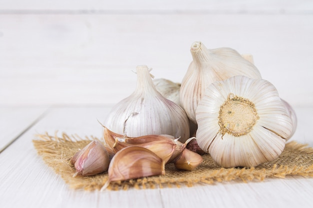 Garlic cloves and garlic bulb on a white wooden table.
