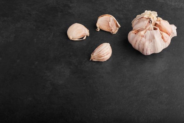 Spicchi d'aglio nell'angolo in alto su sfondo nero.