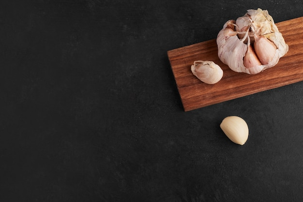 Garlic cloves on a wooden board.