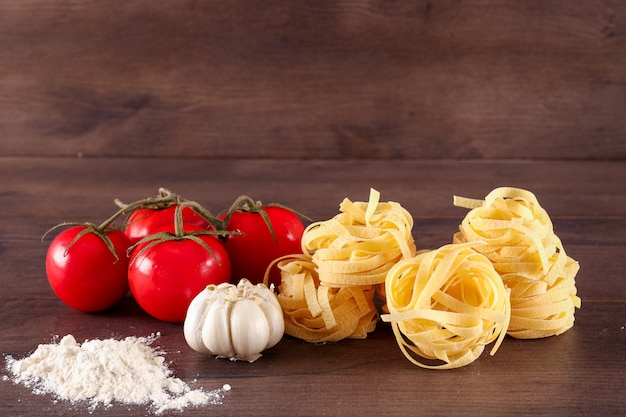 Garlic flour and fresh red cherry tomatoes tagliatelle pasta on wooden surface