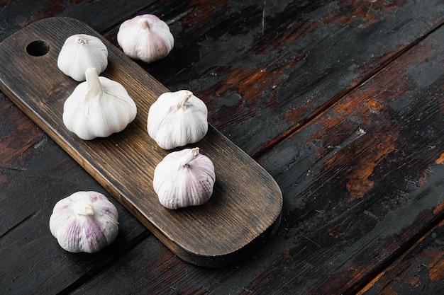ニンニク。新鮮なニンニクセット、木製のまな板、古い暗い木製のテーブル