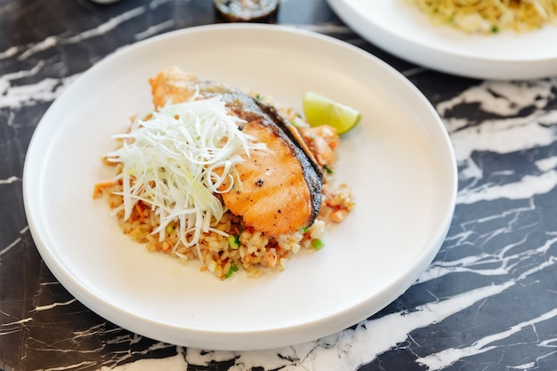 Garlic fried rice with grilled salmon served with chili bean sauce on black marble top table.