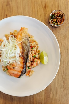 Garlic fried rice with grilled salmon on wooden table background.