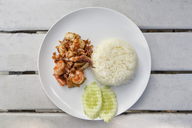 Garlic fried seafood / fried shrimp squid fish with rice on white plate and cucumber