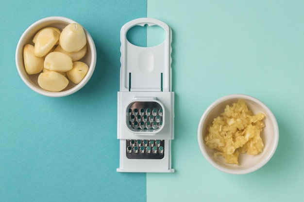 Garlic grater and peeled garlic on a two-color wall. a popular spice for the kitchen.