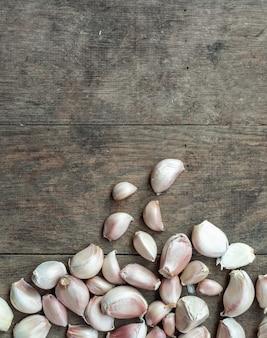Garlic, herb vegetable ingredient on brown wood texture background with copyspace on top, top view.