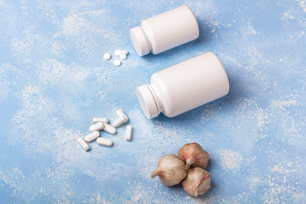 Garlic and herbal supplement pills falling from the medicine bottles