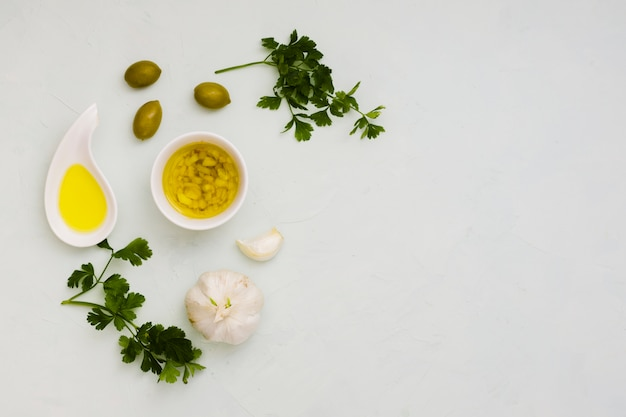 Garlic infused olive with olives and parsley leaves on white background