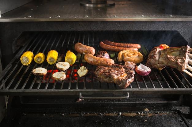 마늘, 양파, 옥수수, 토마토, 소시지와 고기를 그릴에 올려 뜨거운 숯불에 굽습니다.
