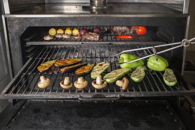 마늘, 양파, 가지, 호박, 버섯, 옥수수, 후추, 토마토 및 고기를 연기와 함께 뜨거운 숯불에 굽습니다.