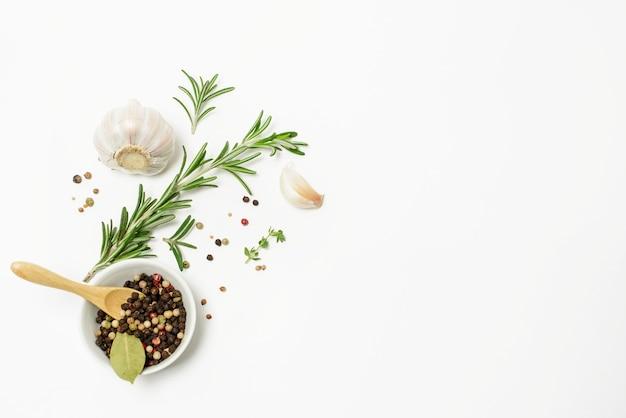 ニンニク、ローズマリー、月桂樹の葉、オールスパイス、コショウを白いスペースで隔離。フラットレイ。上面図