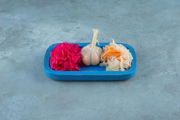 Aglio e crauti su un piatto di legno, sul tavolo di marmo.