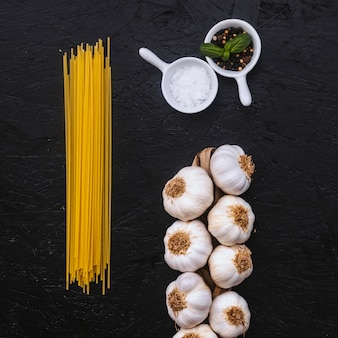 Garlic and spices near spaghetti
