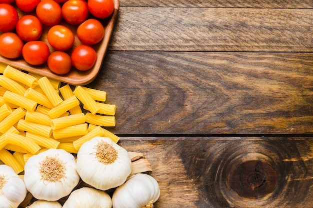 Garlic and tomatoes near pasta Free Photo
