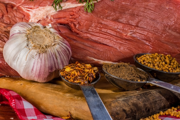 Garlic and various spices accompanying a close-up of piece of meat