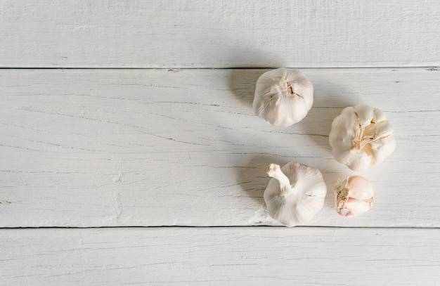 Garlic whole and cloves on wood.