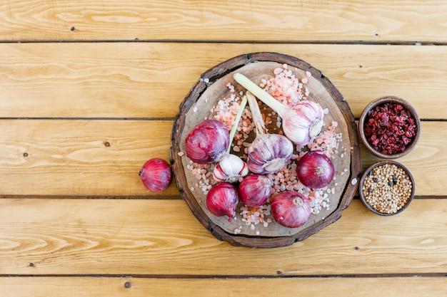붉은 양파, 말린 매자 나무, 암염, 퀴 노아, 후추가 든 마늘은 나무와 도마에 눕습니다.