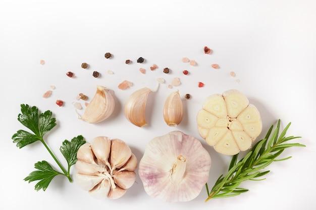 ローズマリー、パセリ、コショウの実が白い表面に分離されたニンニク。上面図。フラットレイ。自家栽培のオーガニックガーデンから採れたて。食品のコンセプト。