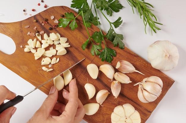 로즈마리, 파 슬 리와 후추의 열매는 흰색 표면에 고립 된 나무 보드에 마늘. 평면도. 평평하다. 가정 성장 유기농 정원에서 갓 골랐습니다. 음식 개념.