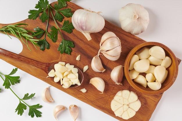 白い表面に分離された木の板にローズマリー、パセリ、コショウの実とニンニク。上面図。フラットレイ。自家栽培のオーガニックガーデンから採れたて。食品のコンセプト。