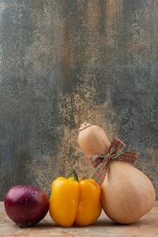 Aglio con peperone giallo e zucca con fiocco su superficie in marmo