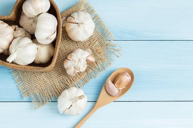 Garlic in a wooden spoon on blue wooden floor,top view