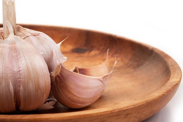 Garlic in wooden tray on wihte background.