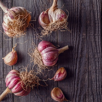 Garlic on wooden vintage background, top view.